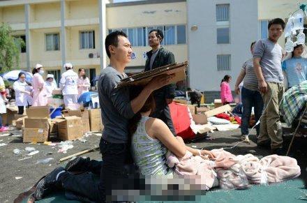 芦山人民医院现场:丈夫跪地给受伤妻子遮阳