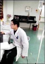 照片中,一名年轻医生左手挂着吊瓶,右手拿着鼠标为病人开医嘱.