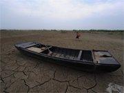 裸露的湖滩上一条小船被湖水抛弃