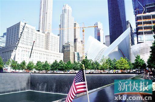 """""""9・11""""遗址,水池边上多了一面美国国旗,一名男子指着水池边上的名字对身旁的孩子说,""""这些人都是英雄。"""""""