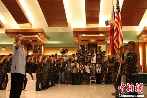 """4月16日,菲律宾与美国""""肩并肩""""联合军事演习正式开幕。图为在菲武装部队总部举行的开幕式上,两国士兵持国旗入场,图左为菲律宾国会国家安全与防务委员会主席比亚松。中新社发 张明 摄"""