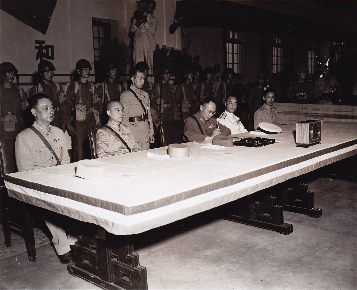 何应钦将军在日本投降协议书以及和平条约上签字。洛布中尉拍摄于南京中央陆军军官学校,1945年9月9日。