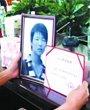 万洲的父亲一手拿着获奖证书一边看着儿子的遗照