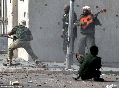 利比亚战场现淡定哥 炮火中弹吉他奏乐曲(图)