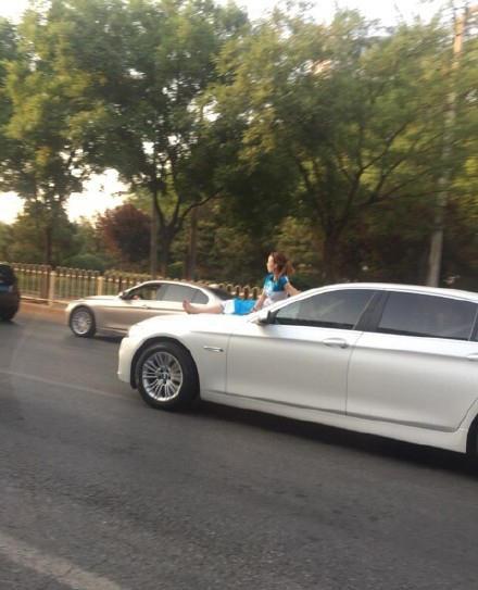 图为坐在轿车引擎盖上的女子。