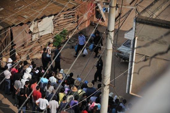 5月9日,警方在嫌犯张永明的家门口拉起了警戒线,并从其家中拎出了多个塑料袋。