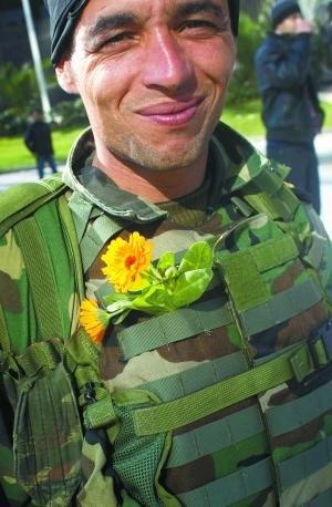 17日,突尼斯,一名佩戴鲜花的士兵,他正参加一场反前总统本·阿里的示威游行。