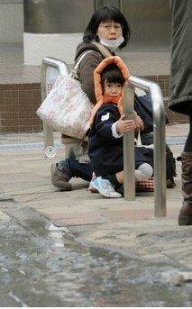 图文:强震恐慌下的一对母女蜷缩在东京街头