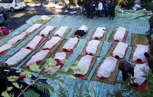 11月11日,云南师宗煤矿事故现场,经过24小时的轮班作业,已有20名遇难者遗体升井。遗体辨认工作正在进行。图为20名遇难者遗体等待亲人辨认。