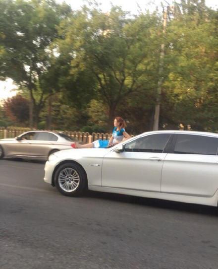 女子坐在轿车引擎盖上行驶而过 惊呆网友