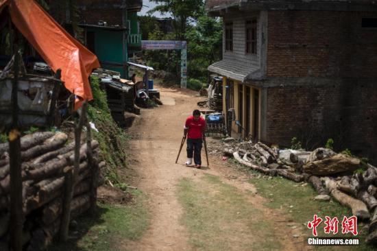 4月30日,一名拄着拐的男子在村里走过。这里是巴斯朗村,位于尼泊尔地震震中廓尔喀县城西郊,全村九成房屋倒塌。中新社发 张浩 摄