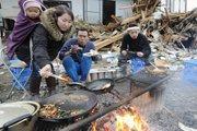一家人在损毁的房屋前煮饭吃