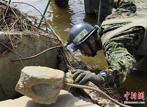 4月27日下午,一名日本自卫队队员在宫城县石卷市大川小学附近的废墟搜寻失踪者。大川小学在此次地震海啸中有77名学生遇难,目前仍由一名教师和8名学生下落不明。中新社记者 侯宇 摄