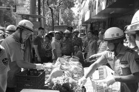 7月11日,浏阳市北正中路,执法人员暂扣张海的水果。这是浏阳市城管局拍摄的执法现场图。