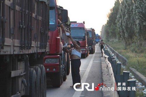 2010年8月16日,京藏高速内蒙古兴和到河北段进京方向,商人向司机出售盒饭。(图片来源:国际在线)