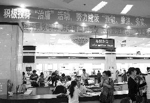 """武汉某政府办公大厅内,挂着宣传""""治庸""""活动的条幅。本报记者 褚朝新 摄"""