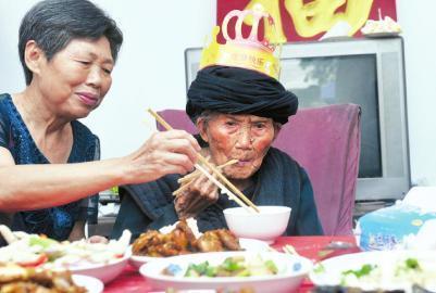 81岁的女儿徐淑华给118岁的母亲夹菜。