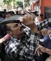 一名示威者拿鞋子敲打印有总统阿萨德头像的海报