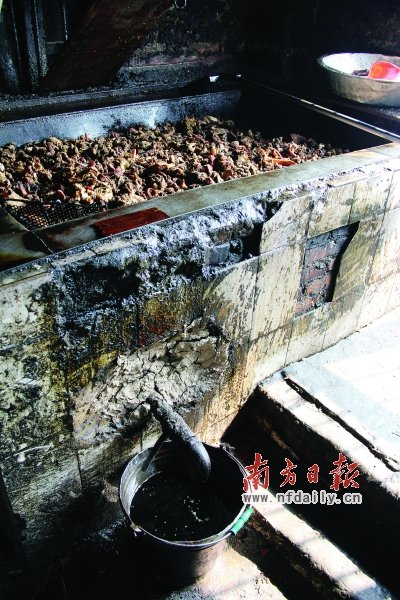 废弃猪肉在土锅里熬炼,黑色的猪油流到桶里。