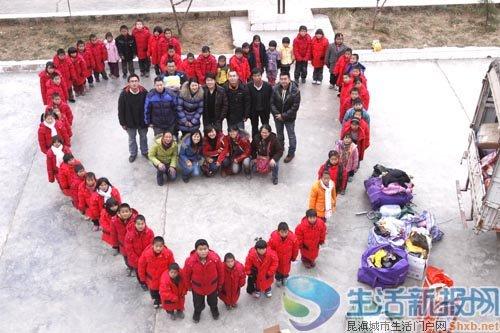 孩子们排成心形和志愿者们合影