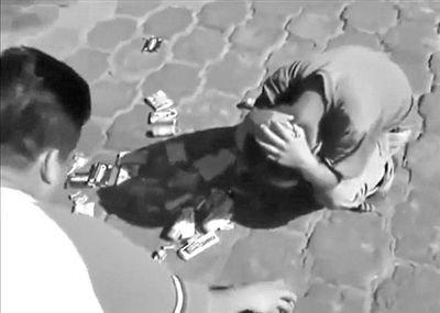 城管走后,曼努尔看到地上的烟和糖果,抱头痛哭。 视频截图