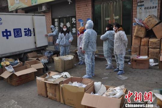 22日,防疫人员在组织分发口罩、胶鞋等防护用品。吕子豪摄