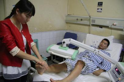 妻子赵一为权亮按摩腿部。