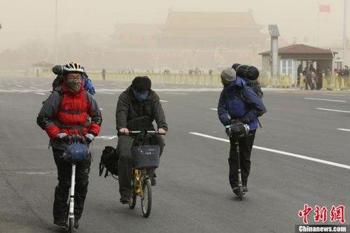 2月28日,几名全身包裹严实的行人骑车经过天安门广场。北京当日再次遭遇严重雾霾天,空气污染严重,能见度差。中午刮起六七级北风,并伴有沙尘。中新社发 盛佳鹏 摄