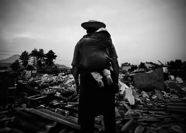 2008年5月22日,四川省彭州市通济镇桥楼村。汶川地震后,59岁的灾民曹良英背着她6个月大的孙子罗远航望着地震被毁的家园。