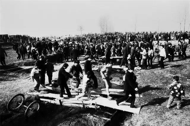 1999年2月28日,河南省宝丰县。赶会的人们通过简易的桥面往返于小河两岸。