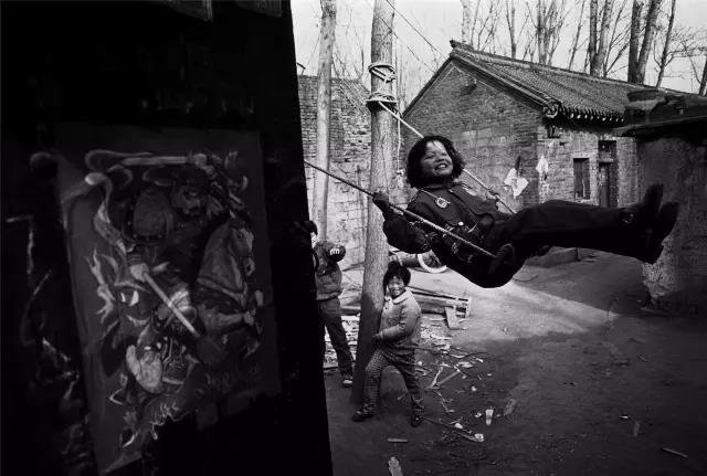 1999年3月2日,河南省伊川县。孩子们在院子的秋千上玩耍。