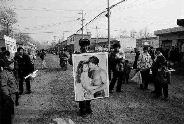 2000年2月3日,河南省伊川县。春节前的年货市场上,一位小贩在向行人展示新潮年画。