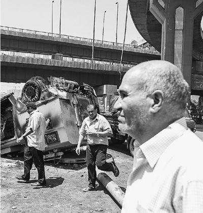 开罗民众在被烧毁的警车旁。