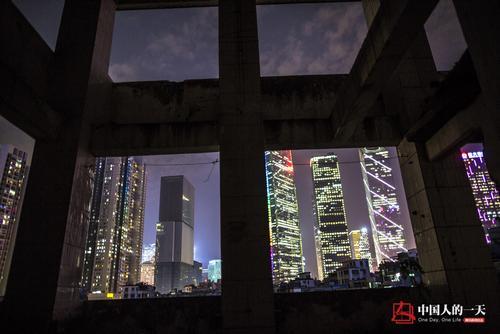 透过冼村一栋已经拆去外墙的建筑,可以看到远处珠江新城的辉煌灯火。张由琼/摄