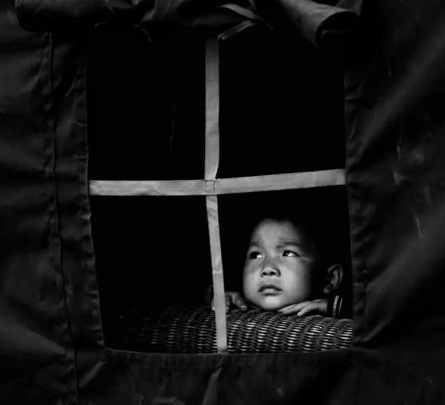 2008年5月22日,四川省彭州市通济镇桥楼村。汶川地震后,地震幸存者6岁的小男孩刘世杰坐在救灾篷里望外看。
