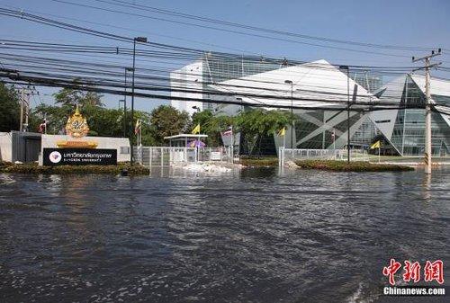 10月19日,洪水再度威胁泰国首都曼谷,曼谷市长素坤攀已要求居住在地势低洼地方的民众撤离。图为当天曼谷市与巴吞他尼府交界处的曼谷大学门前已被洪水围困。中新社发 余显伦 摄