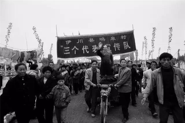 """2002年4月26日,河南省伊川县。农民自发组织""""三个代表""""宣传队到庙会上宣传。""""三个代表""""的内容:中国共产党必须始终代表中国先进生产力的发展要求,代表中国先进文化的前进方向,代表中国最广大人民的根本利益。"""