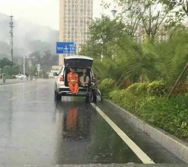 警察打开车后尾箱盖 陪环卫工一起避雨(图)