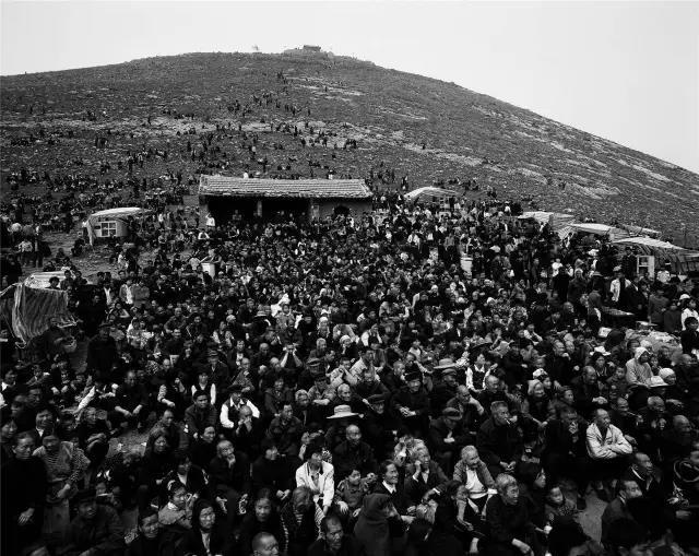 2003年4月4日,河南省宜阳县。乡村庙会上,人们聚集在山坡上观看县剧团的演出。