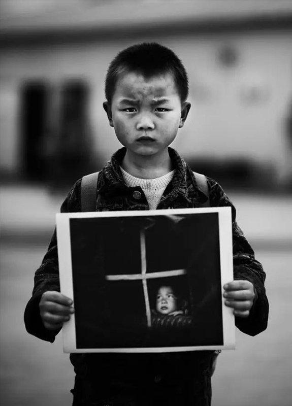 """2009年5月6日,四川省彭州市通济镇中心学校。""""汶川地震""""1周年,地震幸存者7岁的刘世杰拿着地震后在救灾篷的照片。现在,他是镇中心学校学前班学生。"""