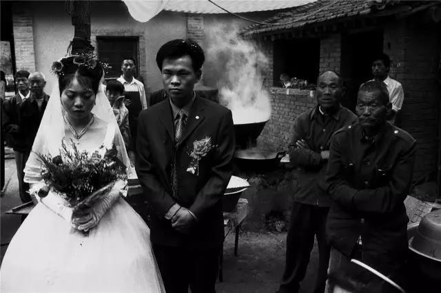 2003年5月16日,河南省孟津县。新郎张向辉和新娘贾艳艳在乡村婚礼仪式上。由于当时正值预防非典的紧张时期,凡是聚众活动都必须减少或取消。即使村民举行婚礼,也要上报乡政府同意才行。同时,村里要对婚礼现场的外来人员进行认真消毒,对举办婚礼的时间和参加婚宴的人数严格控制。