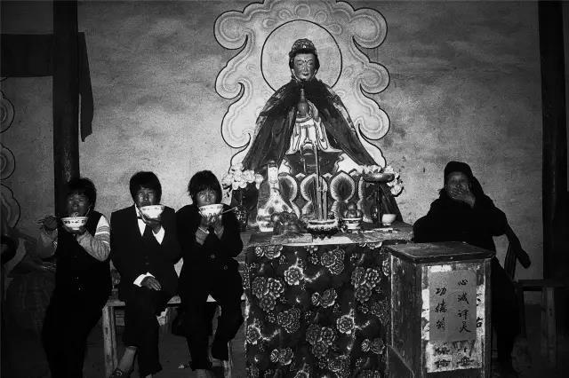 2004年5月3日,河南省伊川县。在寺庙里守护神像的人们。