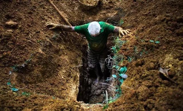 掘墓人正在挖掘一块82年前的坟墓。政府建议把这座墓园的一部分划分出来建一条8车道公路和高楼。