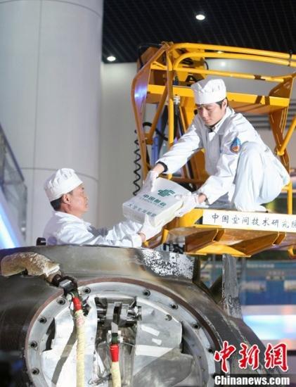 """11月21日,神舟八号返回舱开舱仪式在北京航天城举行,图为工作人员在开舱取出包裹,取出由专用""""太空邮局""""邮袋包裹的搭载物品。 中新社发 张浩 摄"""