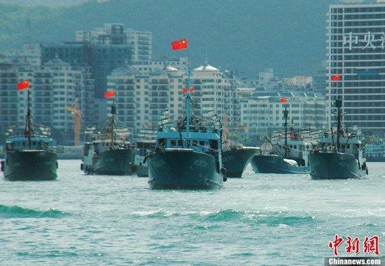 7月12日上午9时许,海南省30艘渔船自发组成2个编队6个小组的捕捞船队,从三亚出发前往南沙开展捕捞生产活动。该航次作业时间约20天,生产地点在北纬10°永暑礁附近海域。海南省捕捞船队本次赴三沙渔场生产作业,是渔业企业、合作社、渔民三方抱团合力闯深海。这是海南省历年来最大规模的捕捞活动之一。中新社发 尹海明 摄