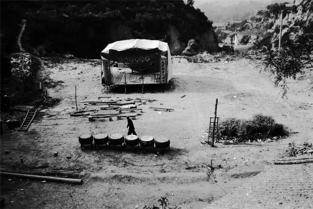 2004年5月6日,河南省孟津县。一位老人从演出结束的戏台和大鼓前走过。