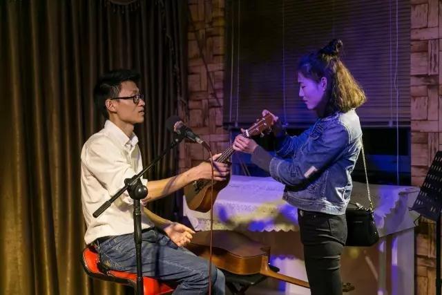 在肖宇曾经打工的琴行里,一位女孩向他请教弹吉他的问题。