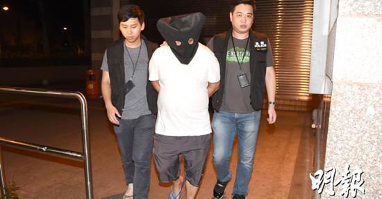 涉嫌斩人男子被警方拘捕,黑布蒙头,带回警署。图自香港《明报》网站