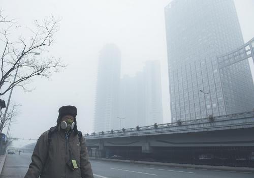图片说明:29日,一名行人戴面具在北京的雾霾天气中出行。