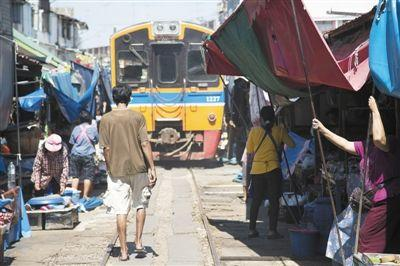 2014年4月21日,泰国美功,小贩赶在火车到来前收拾货物。泰国铁路十分老旧,全部为窄轨铁路,时速仅50公里左右,在贫民区经常能见到铁道市场。